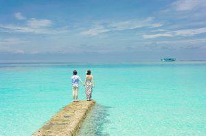 deux personnes sur ponton devant mer turquoise