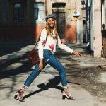 femme qui marche dans la rue avec pull blanc jean et bottines velours