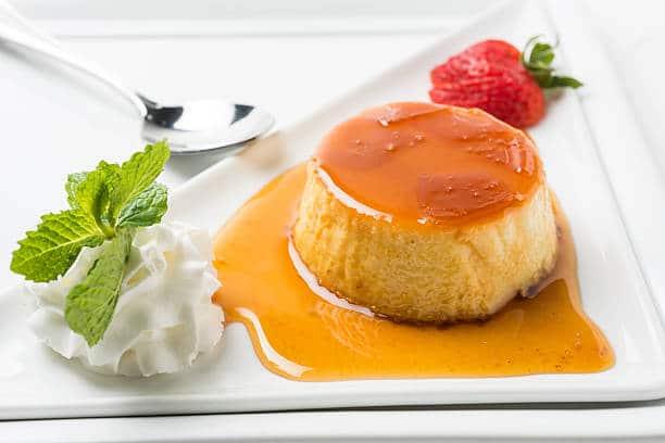 Flan coco-caramel dans une assiette à dessert avec de la chantilly et des fraises