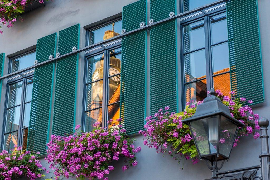 façade avec fenêtres aux volets verts et jardinières de fleurs roses