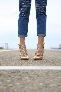 zoom sur le bas des jambes d'une femme qui porte un jean avec des clous et des escarpins nude à brides avec des clous
