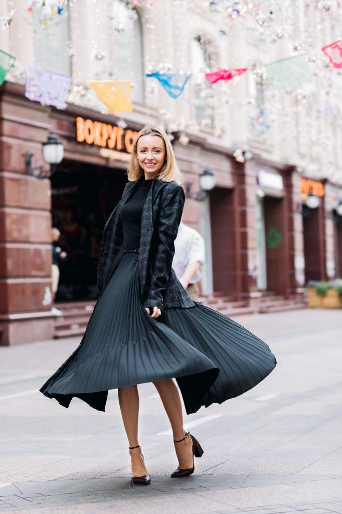 femme blonde dans la rue portant une jupe midi foncée un pull noir et une veste de blazer à carreaux