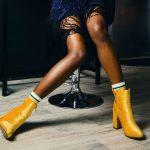 jambes de femme avec bottines jaunes et chaussettes blanches et noire