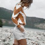 femme avec short beige, pull blanc et camel et cuissardes camel