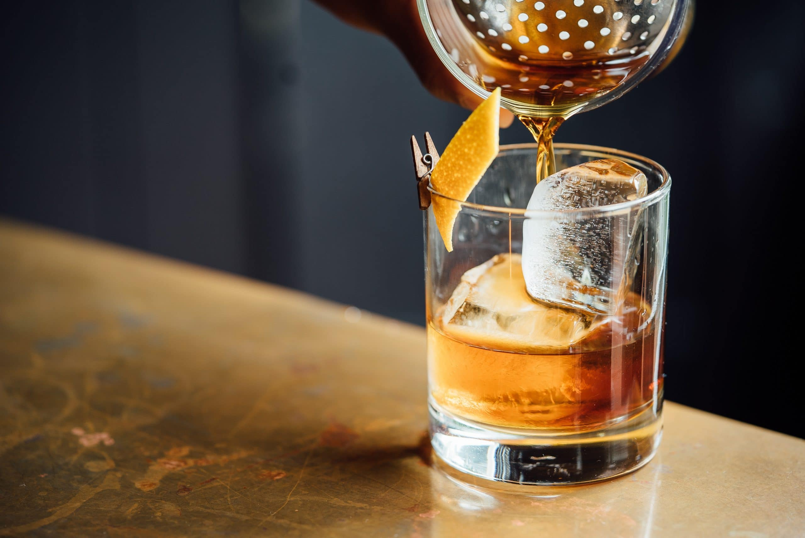 Verre de whisky avec glaçons et zeste d'orange