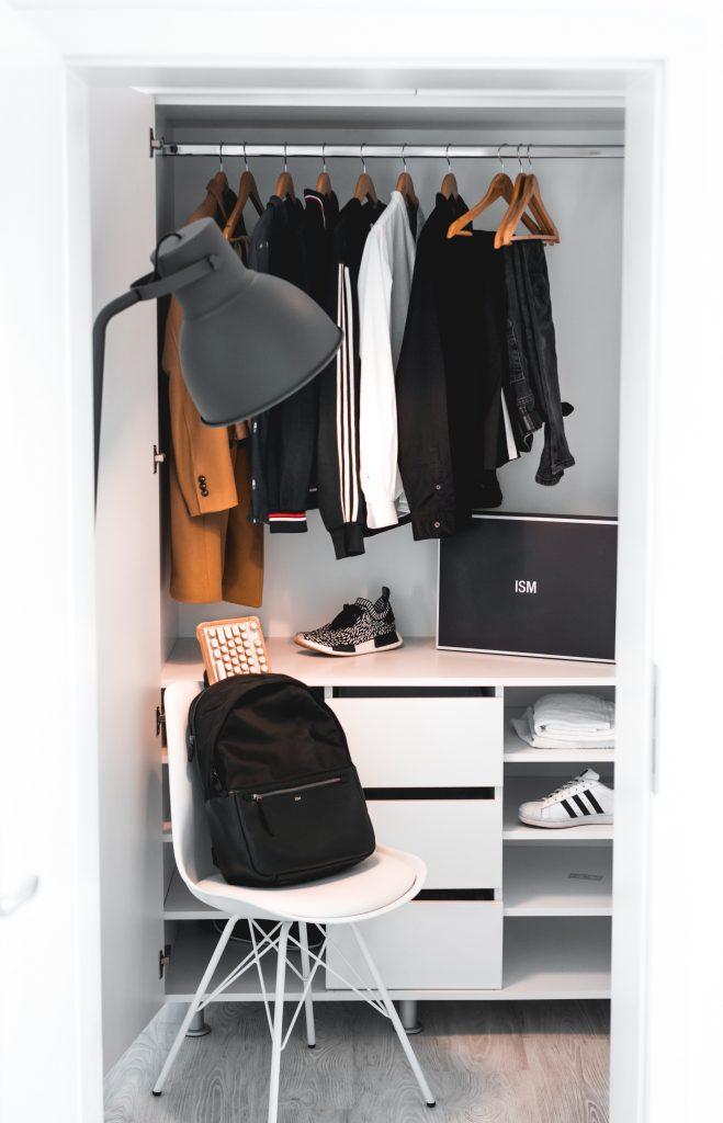 dressing avec penderie et étagères et une chaise avec un sac à dos