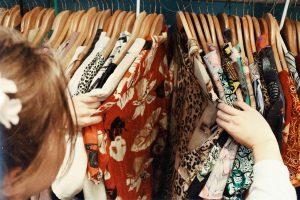 femme qui fait du shopping et regarde des vêtements sur des cintres