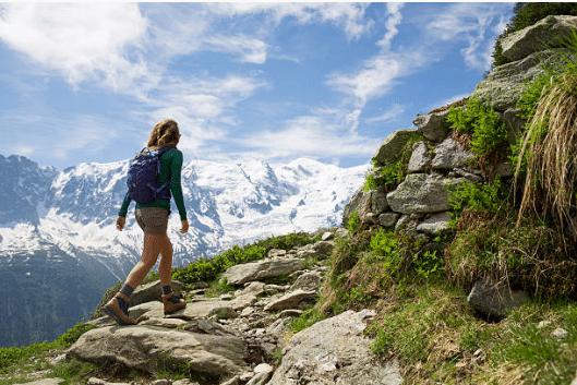 femme qui randonne dans la montagne par beau temps avec vue sur les montagnes enneigées