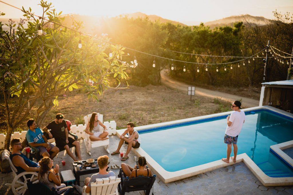 extérieur avec piscine et guirlande lumineuse groupe de personnes assises près de la piscine buvant un verre