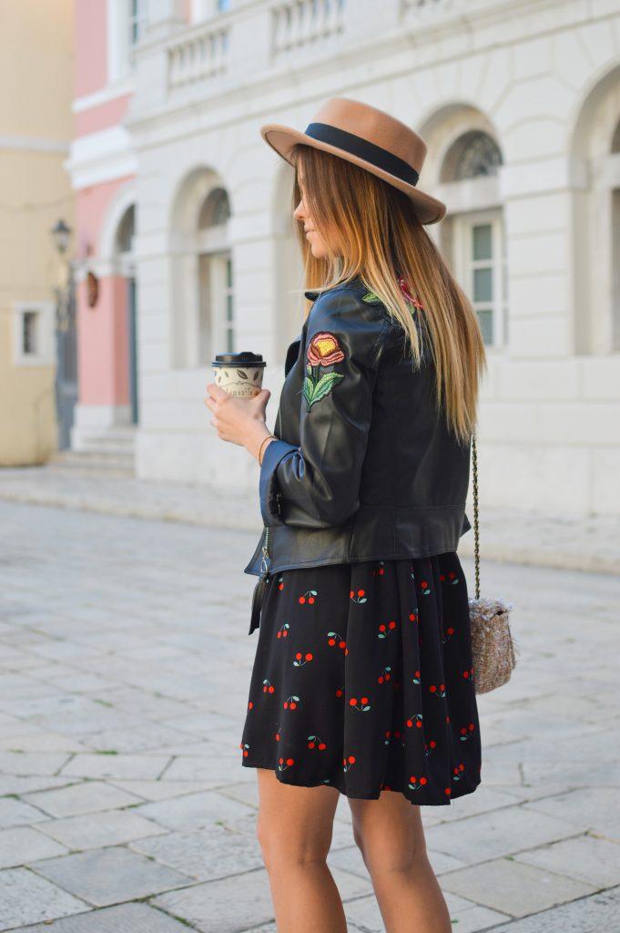 femme blonde aux cheveux longs portant une veste en cuir noir sur une robe courte noire avec un motif cerises