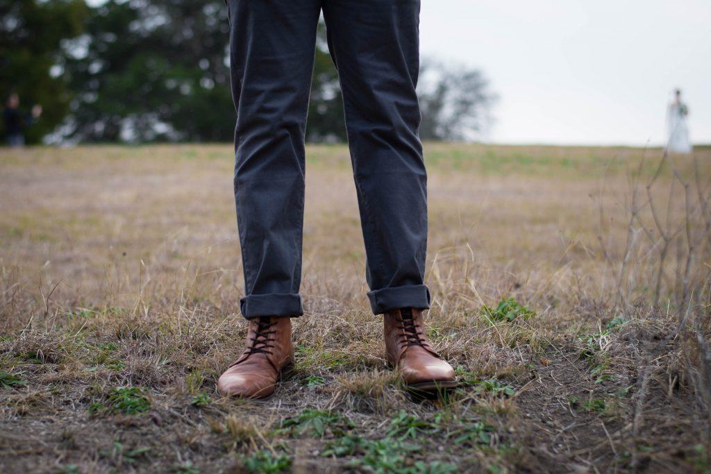 jambes d'un homme portant un pantalon sombre et des bottines à lacets marron