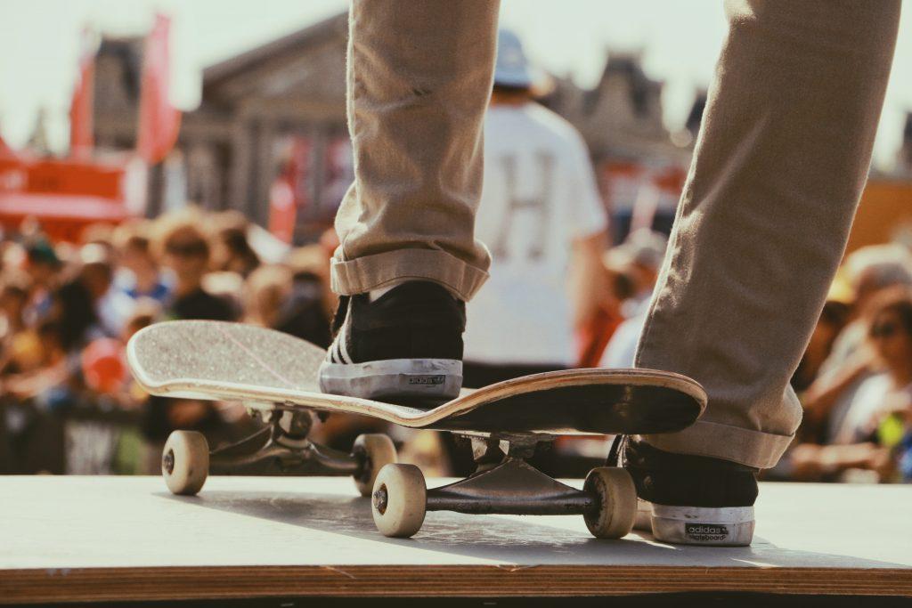 bas des jambes d'un homme portant un pantalon chino beige des baskets noires et blanches avec un pied sur un skate