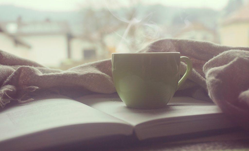 tasse avec boisson chaude fumante posée sur un livre