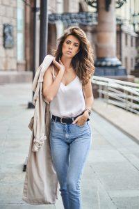 femme portant un jean un top blanc et un trench camel