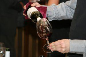 Sommelier qui remplit un verre de vin rouge bio