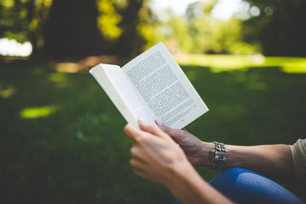 Jeune femme qui lit un livre young adult de fantasy dans un parc