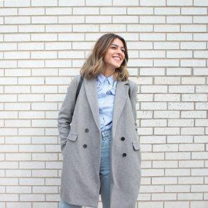 femme portant un manteau long gris un chemisier bleu et un jean devant un mur en briques blanches