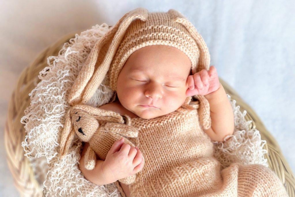Bébé avec un bonnet et un doudou lapin tricotés