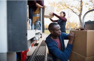 personnes chargeant des cartons de déménagement dans un camion